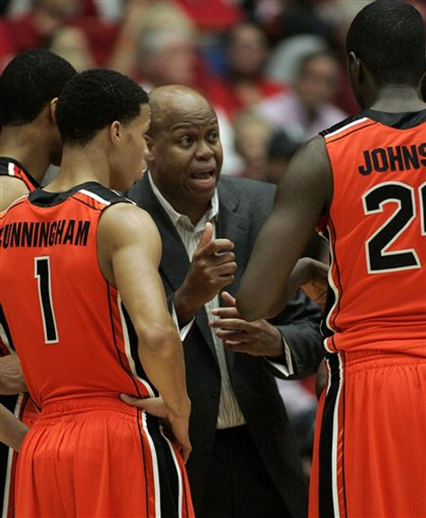 Oregon States' head coach Craig Robinson, center, talks to Omari Johnson (24) about his playing, while Jared Cunningham listens during the second half of an NCAA college basketball game against Arizona at McKale Center in Tucson, Ariz., Thursday, Mar. 3, 2011. Arizona won 70 - 59. (AP Photo/John Miller)