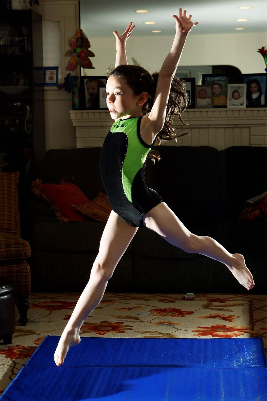 Amalya Knapp does warm-up exercises at her family's home in Teaneck, N.J. The 7-year-old's family is upset with USA Gymnastics because it did not allow her scores to count toward any title or rankings because her Orthodox Jewish faith did not allow her to compete in the Saturday finals. (Associated Press)