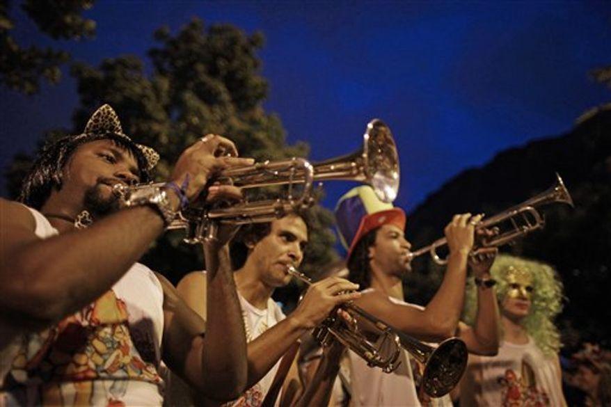 Brazilian supermodel Gisele Bundchen, left, talks with her husband, U.S. football player Tom Brady, during a carnival parade at the Sambadrome in Rio de Janeiro, Brazil, early Monday March 7, 2011. (AP Photo/Rodrigo Abd)