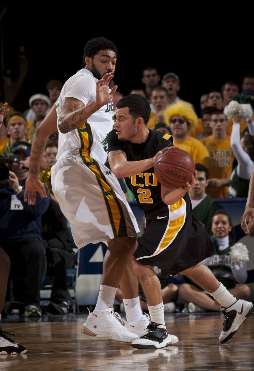 VCU's Joey Rodriguez, right, moves against George Mason's Ryan Pearson, left, during Game 9 of the NCAA college Colonial Athletic Association college basketball tournament in Richmond, Va., Sunday, March 6, 2011. (AP Photo/Scott K. Brown)
