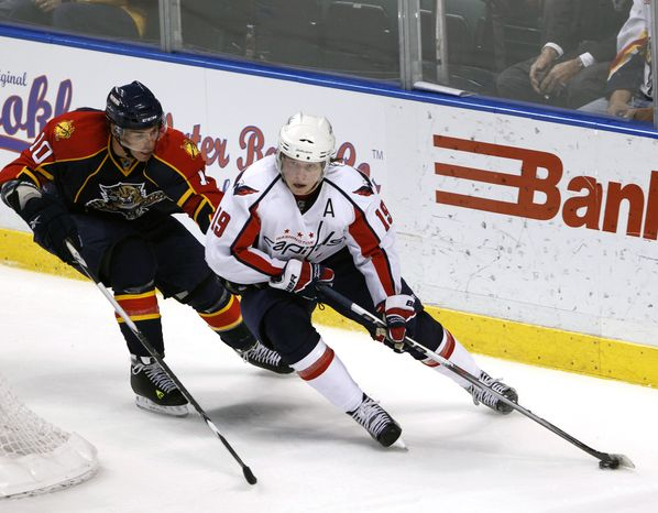 Florida Panthers left wing David Booth, left, and Washington Capitals center Nicklas Backstrom battle for the puck during the first period of an NHL hockey game on Sunday, March 6, 2011, in Sunrise, Fla. (AP Photo/Wilfredo Lee)