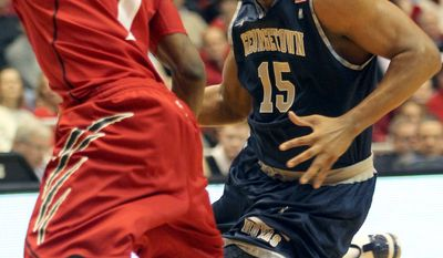 **FILE** Georgetown's Austin Freeman (right) drives to the basket past Cincinnati's Cashmere Wright during the second half of an NCAA college basketball game on March. 5, 2011. (Associated Press)