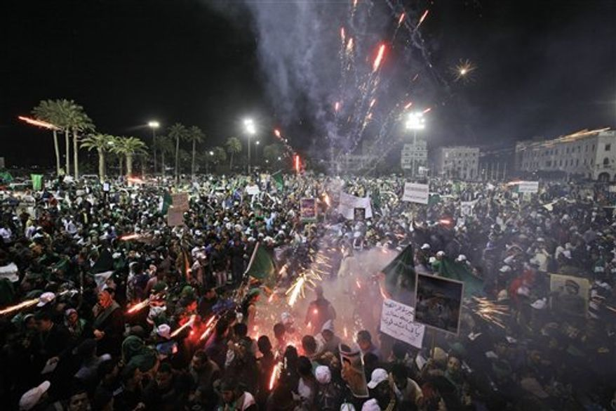 Pro-Gadhafi supporters set off fireworks at an organised rally in Green Square, Tripoli, Libya Friday, March 4, 2011. In Tripoli, Gadhafi loyalists fired tear gas and live ammunition to smother a new outbreak of protests, while thousands of Gadhafi supporters later packed into the capital's central Green Square, waving green flags and pictures of the Libyan leader in a counterdemonstration complete with fireworks. (AP Photo/Ben Curtis)