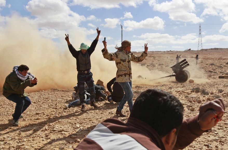 Libyan rebels who are part of the forces against Libyan leader Moammar Gadhafi fire a rocket launcher Sunday as they battle Gadhafi's troops outside the town of Bin Jawwad in eastern Libya. Libyan helicopter gunships fired on a rebel force advancing west toward the capital along the Mediterranean coastline Sunday and forces loyal to leader Moammar Gadhafi fought intense ground battles with the rival fighters. (Associated Press)
