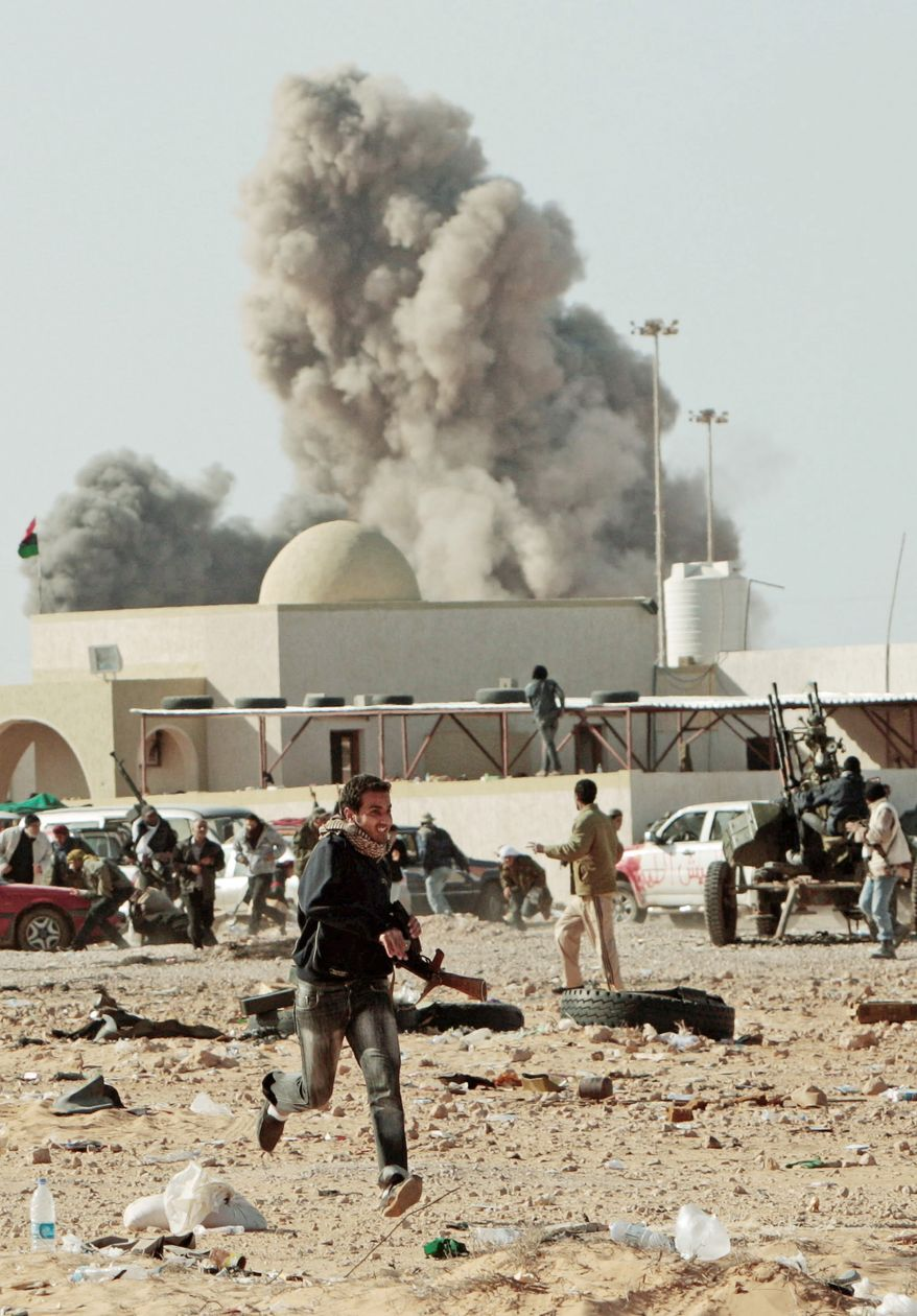 An anti-Gadhafi rebel runs away as smoke rises following an airstrike by Libyan warplanes in Ras Lanouf, Libya, a key oil port on the Mediterranean coast, on Monday. (Associated Press)