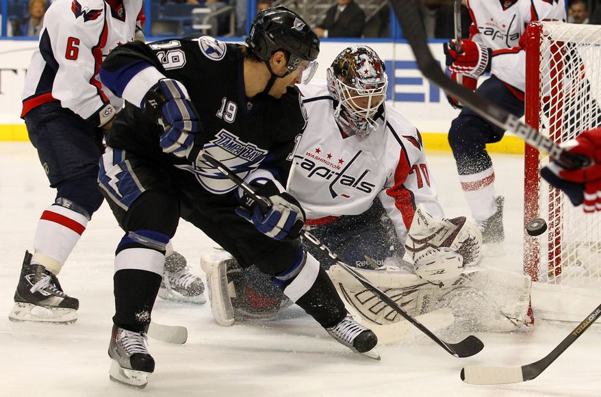 **FILE** Washington Capitals goalie Braden Holtby (right) makes a save on a shot from Tampa Bay Lightning's Dominic Moore during the second period of an NHL hockey game on March 7, 2011, in Tampa, Fla. (Associated Press)