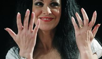 "FILE - In this July 20, 2010 file photo, Romanian soprano Angela Gheorghiu  gestures during news conference with at the Royal Opera House in Madrid.  The Met announced Monday, March 7, 2011, that Gheorghiu had pulled out of the Des McAnuff ""Faust"" for ""artistic reasons.""  (AP Photo/Paul White, file)"