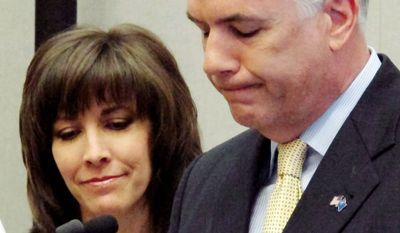 """Sen. John Ensign, Nevada Republican, accompanied by his wife, Darlene, announces he will not run for a third term at a news conference Monday in Las Vegas. He called it """"the most difficult decision that I have ever made."""" (Associated Press)"""