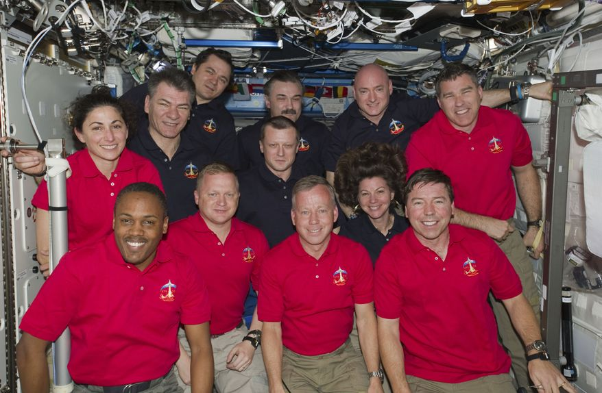 Inside the U.S. space lab Destiny, 12 astronauts and cosmonauts take a break from a very busy week aboard the International Space Station to pose for a joint STS-133 (space shuttle Discovery)/Expedition 26 (ISS) group portrait on Thursday, March 3, 2010. The STS-133 crew members, attired in red shirts, are (from left) NASA astronauts Nicole Stott, Alvin Drew, Eric Boe, Steve Lindsay, Michael Barratt and Steve Bowen. The dark-blue-attired Expedition 26 crew members (from left) are European Space Agency astronaut Paolo Nespoli; Russian cosmonauts Oleg Skripochka, Dmitry Kondratyev (below) and Alexander Y. Kaleri; and NASA astronauts Scott Kelly and Cady Coleman (below). (AP Photo/NASA)