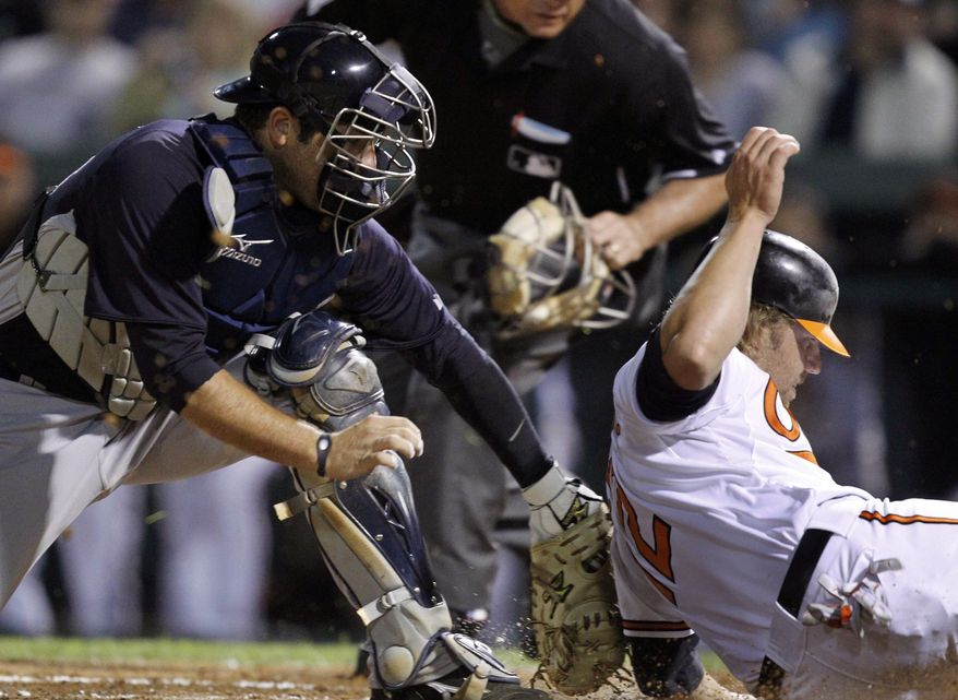 Baltimore Orioles' Mark Reynolds, right, is tagged out by New York Yankees catcher Austin Romine during the second inning of a spring training baseball game in Sarasota, Fla., Monday, March 7, 2011. Reynolds was trying to score on a double by Adam Jones. (AP Photo/Gene J. Puskar)
