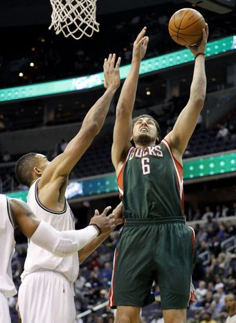 Milwaukee Bucks' Andrew Bogut (6), of Australia, shoots and scores against Washington Wizards' JaVale McGee (34) during the first half of an NBA basketball game in Washington, Tuesday, March 8, 2011. (AP Photo/Manuel Balce Ceneta)