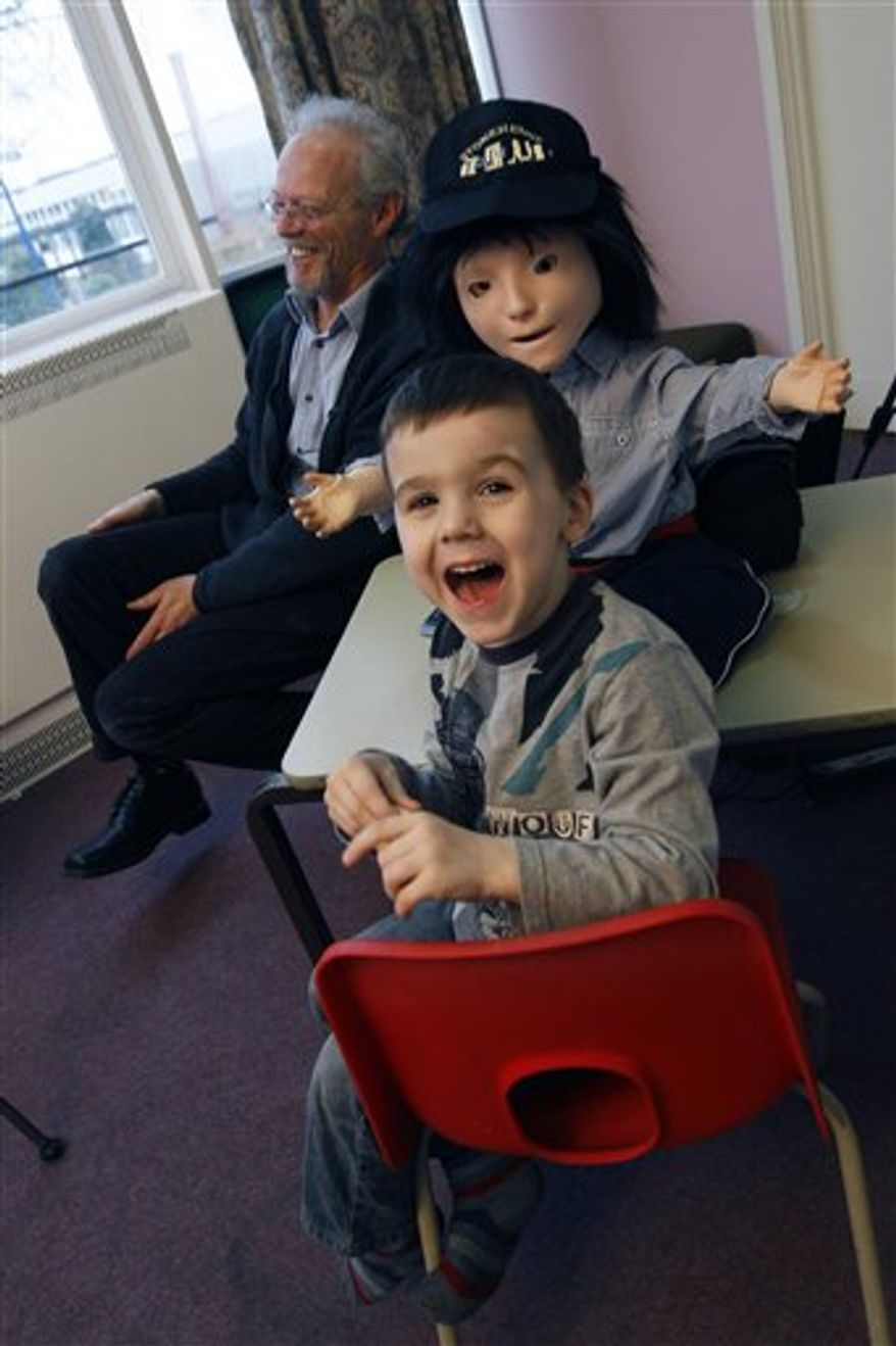 In this Monday, Feb. 28, 2011 photo, Dr Ben Robins, right, a research fellow at Hertfordshire University shows off two 'Kasper' robots that he hopes will help with autistic children, in Hatfield, England. Autistic children play with the robot for up to 10 minutes alongside a scientist who controls the robot with a remote control.   The robot, named Kaspar, is programmed to do things like smile, frown, laugh, blink and wave his arms. He has shaggy black hair, a baseball cap, a few wires protruding from his neck, and striped red socks. He was built by scientists at the University of Hertfordshire at a cost of about 1,300 pounds ($2,118). (AP Photo/Alastair Grant)