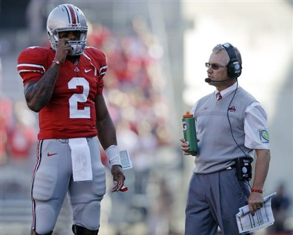 FILE - In this Sept. 25, 2010 file photo, Ohio State's Terrelle Pryor, left, and coach Jim Tressel talk during a time out against Eastern Michigan in the second quarter of an NCAA college football game in Columbus, Ohio. Ohio State athletic director Gene Smith has returned to campus and a news conference has been called for Tuesday night, March 8, 2011, signs that coach Tressel's job might be in jeopardy after a report that he did not tell his superiors that he was aware of potential NCAA violations involving star quarterback Terrelle Pryor and others.  (AP Photo/Jay LaPrete, File)