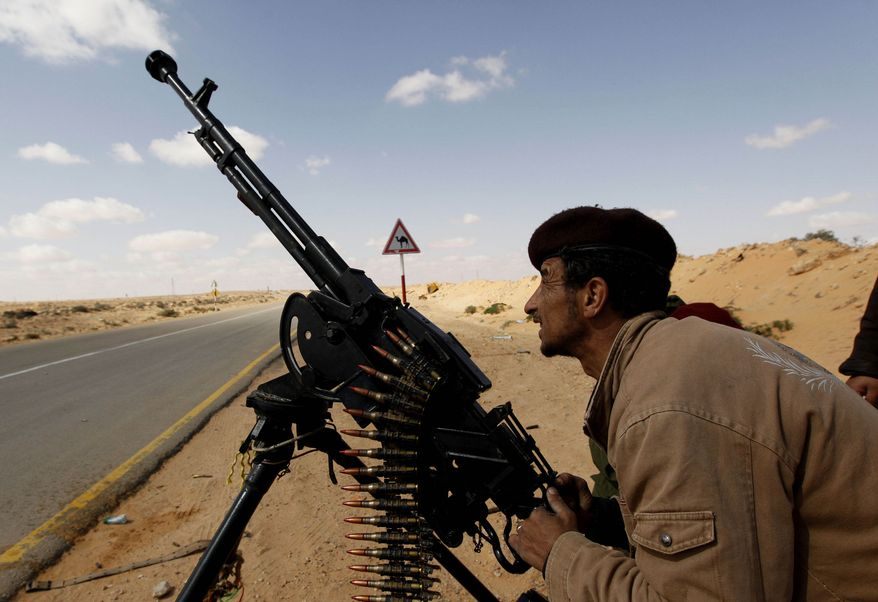 An anti-Gadhafi rebel fires his anti-aircraft machine gun against warplanes of Col. Moammar Gadhafi's regime in the oil port of Ras Lanouf, Libya, on Tuesday, March 8, 2011. The warplanes launched at least three new airstrikes Tuesday near rebel positions, keeping up a counteroffensive to prevent the opposition from advancing toward Col. Gadhafi's stronghold in Tripoli, the capital. (AP Photo/Hussein Malla)