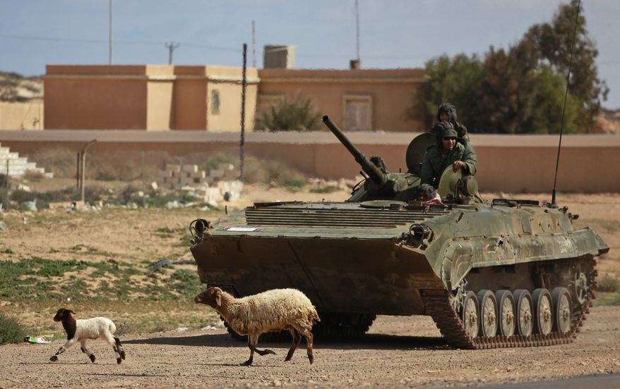 Libyan rebels who are part of the forces against Libyan leader Moammar Gadhafi ride on an armored carrier near Ras Lanuf, eastern Libya, Monday, March 7, 2011. (AP Photo/Kevin Frayer)