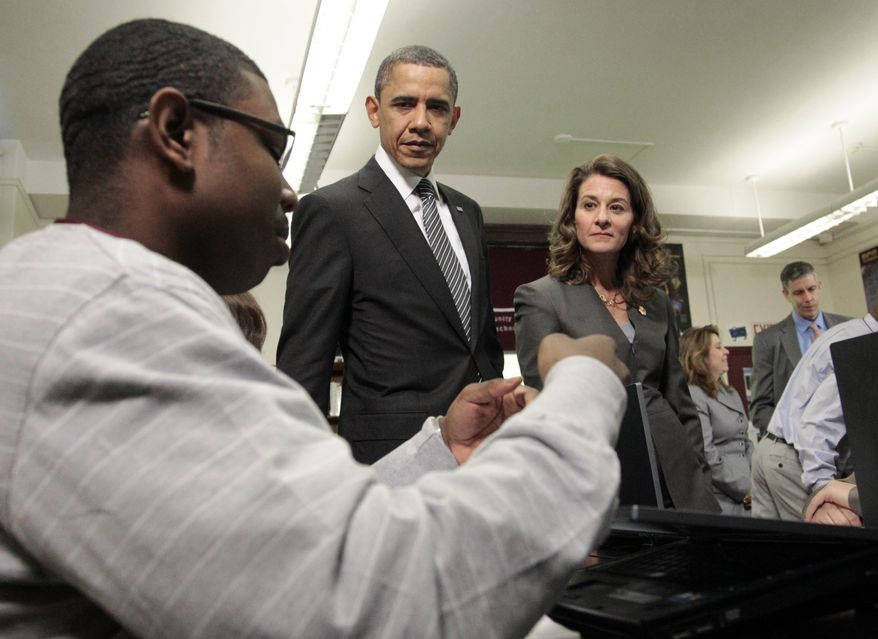 President Obama watches a student Tuesday during his visit to classrooms at TechBoston Academy in Boston. Melinda Gates (center) is the co-chair of the Bill and Melinda Gates Foundation. (Associated Press)