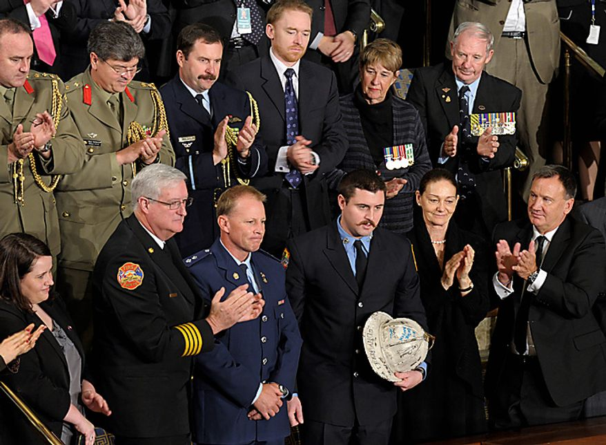 Australian firefighter Rob Frey, third from front left, and New York City firefighter James Dowdell, holding helmet, are recognized in a speech by Australian Prime Minister Julia Gillard, not pictured, during an address at a joint meeting of Congress on Capitol Hill in Washington, Wednesday, March 9, 2011. Mr. Frey participated in a joint exercise with New York City and Australian firefighters before the Sydney Olympics with Mr. Dowdell's father, Kevin Dowdell. Kevin Dowdell later died in the 9/11 attacks and Mr. Frey then returned the helmet to Mr. Dowdell's family. (AP Photo/Susan Walsh)