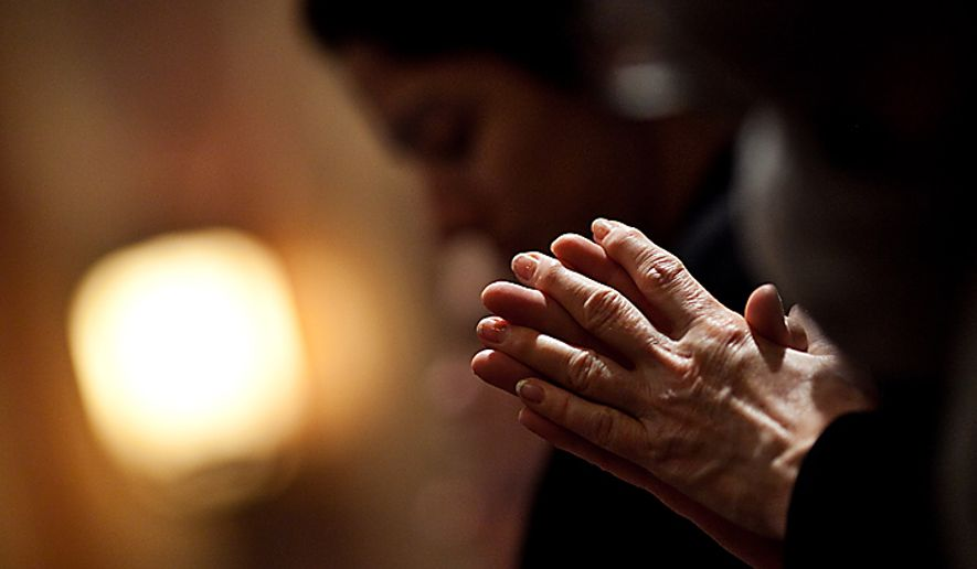 Marsha Zamperini, of Washington, folds her hands in prayer during Ash Wednesday Mass at the Cathedral of St. Matthew the Apostle, on Rhode Island Avenue in northwest Washington, Wednesday, March 9, 2011. (Drew Angerer/The Washington Times)