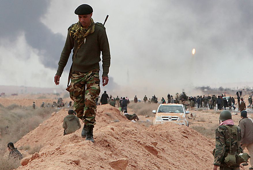 An anti-Gadhafi rebel walks along a sand barrier as other rebels fire a rocket launcher seen in the right during  fighting against pro-Gadhafi fighters, in Sedra, eastern Libya, Wednesday March 9, 2011. A high-ranking member of the Libyan military flew to Cairo on Wednesday with a message for Egyptian army officials from Moammar Gadhafi, whose troops pounded opposition forces with artillery barrages and gunfire in at least two major cities. Col. Gadhafi appeared to be keeping up the momentum he has seized in recent days in his fight against rebels trying to move on the capital, Tripoli, from territory they hold in eastern Libya. (AP Photo/Hussein Malla)