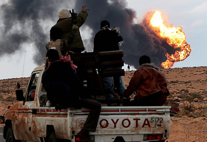 An anti-Moammar Gadhafi rebel sit next to a mulitiple rockets launcher as flames rises from a fuel storage facility that attacked during a fighting against pro-Gadhafi fighters, in Sidr town, eastern Libya, on Wednesday, March 9, 2011. A high-ranking member of the Libyan military flew to Cairo on Wednesday with a message for Egyptian army officials from Col. Gadhafi, whose troops pounded opposition forces with artillery barrages and gunfire in at least two major cities. Col. Gadhafi appeared to be keeping up the momentum he has seized in recent days in his fight against rebels trying to move on the capital, Tripoli, from territory they hold in eastern Libya. (AP Photo/Hussein Malla)