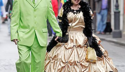 Richard Porter and his wife Jennifer stroll trough the streets of the French Quarter during Mardi Gras celebrations in New Orleans Tuesday, March 8, 2011. The Porters met at the Mardi Gras celebration 22-years ago. (AP Photo/Bill Haber)