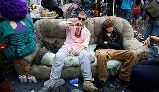 A reveler takes a sip of bourbon as he sits next to a sleeping man on a couch during the Zulu Social Aid and Pleasure Club parade on St. Charles Avenue in New Orleans on Mardi Gras Day, Tuesday, March 8, 2011. (AP Photo/Patrick Semansky)