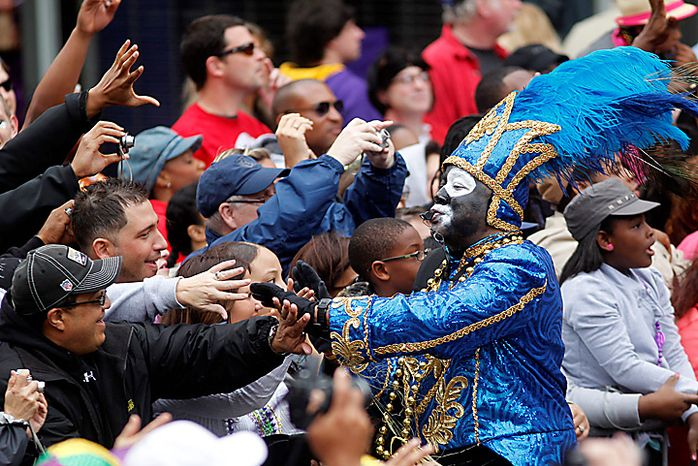 A member of the Krewe of Zulu interacts with revelers on Canal St. on Mardi Gras Day in New Orleans, Tuesday, March 8, 2011. (AP Photo/Gerald Herbert)