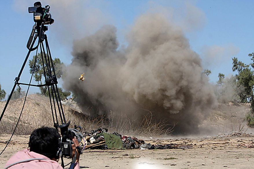 A Pakistani cameraman films an explosion as security forces blow up explosives found at the site of a suicide bomb blast in Matani near Peshawar, Pakistan, on Wednesday, March 9, 2011. A suicide bomber attacked a funeral attended by anti-Taliban militiamen in northwest Pakistan killing many people and wounding more than 100 others, police said. (AP Photo/Mohammad Sajjad)