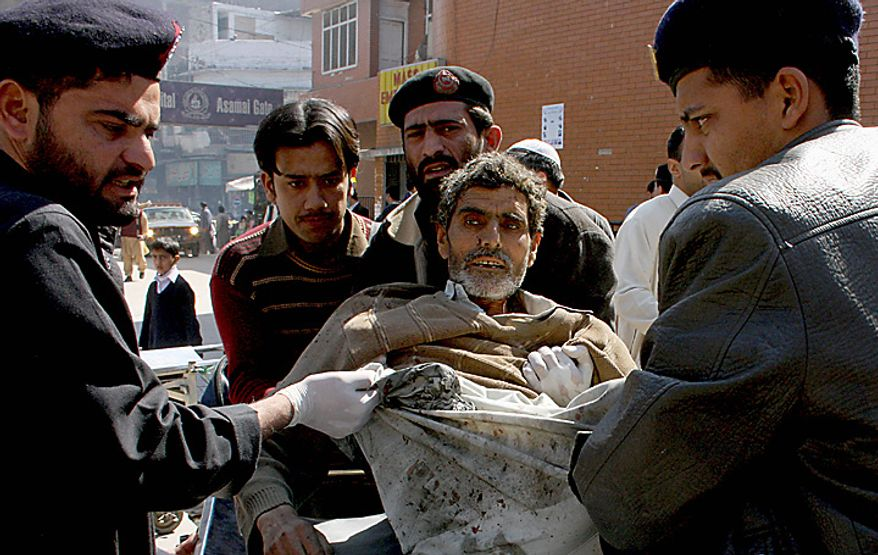 Pakistani hospital staff help a person injured in a suicide attack, at a local hospital in Peshawar, Pakistan, on Wednesday, March 9, 2011. A suicide bomber attacked a funeral attended by anti-Taliban militiamen in northwest Pakistan killing many mourners and wounding more than 100 others, police said. (AP Photo/Mohammad Iqbal)