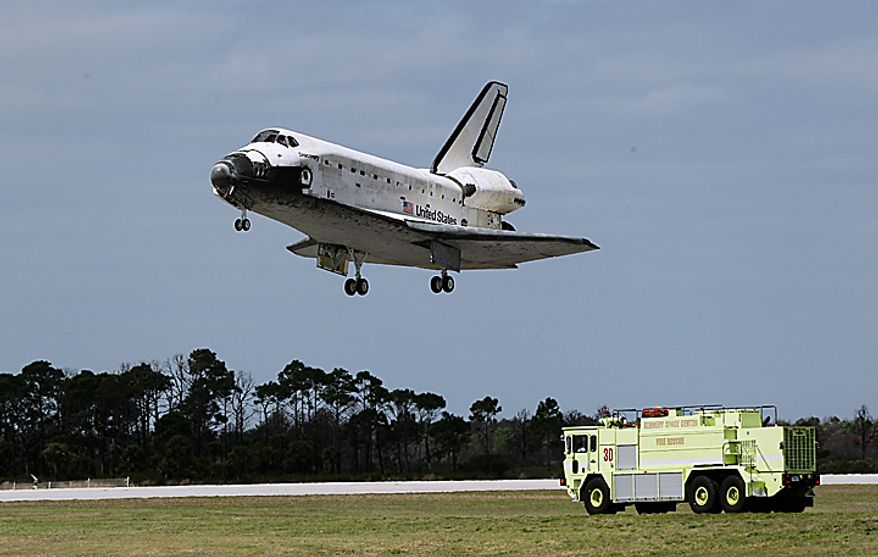 An emergency vehicle stands by near the runway as space shuttle Discovery lands at the Kennedy Space Center in Cape Canaveral, Fla., Wednesday, March 9, 2011. (AP Photo/John Raoux)