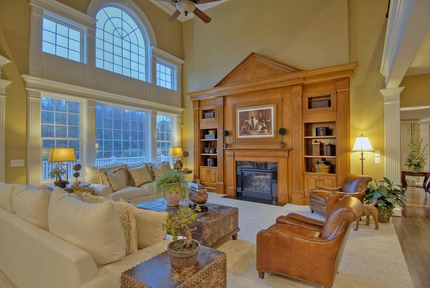 The two-story family room in the Mount Vernon model has a wall of windows, a fireplace and a built-in entertainment center.