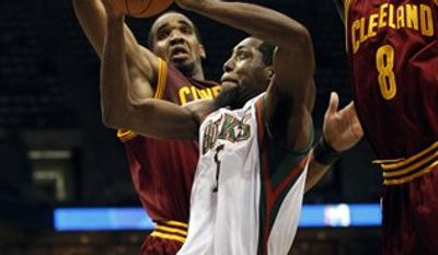 Milwaukee Bucks' John Salmons, center, is fouled as he drives between Cleveland Cavaliers' Samardo Samuels, left, and Christian Eyenga (8) during the second half of an NBA basketball game on Wednesday, March 9, 2011, in Milwaukee. (AP Photo/Morry Gash)
