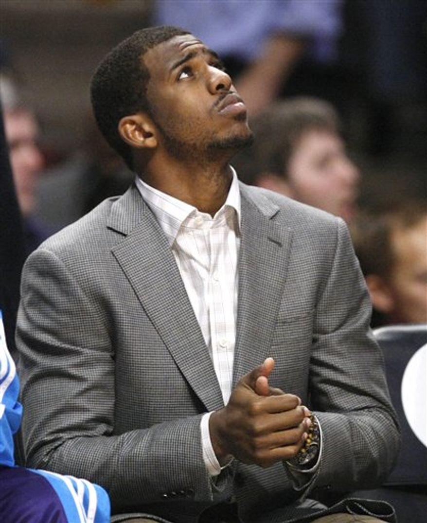 New Orleans Hornets point guard Chris Paul looks up from the bench during the first half of the Hornets' NBA basketball game against the Chicago Bulls on Monday, March 7, 2011, in Chicago. Paul is recovering from a concussion. (AP Photo/Charles Rex Arbogast)