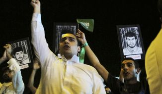 "**FILE** Saudi Shi'ite protesters hold Saudi flags and portraits of unidentified Saudi Shi'ite prisoners during a demonstration in Qatif, Saudi Arabia, on March 9, 2011. Activists in Saudi Arabia's Shi'ite Muslim minority have issued Internet calls for a ""Day of Rage."" (Associated Press)"
