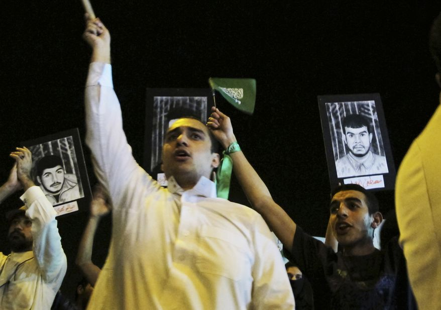 """**FILE** Saudi Shi'ite protesters hold Saudi flags and portraits of unidentified Saudi Shi'ite prisoners during a demonstration in Qatif, Saudi Arabia, on March 9, 2011. Activists in Saudi Arabia's Shi'ite Muslim minority have issued Internet calls for a """"Day of Rage."""" (Associated Press)"""