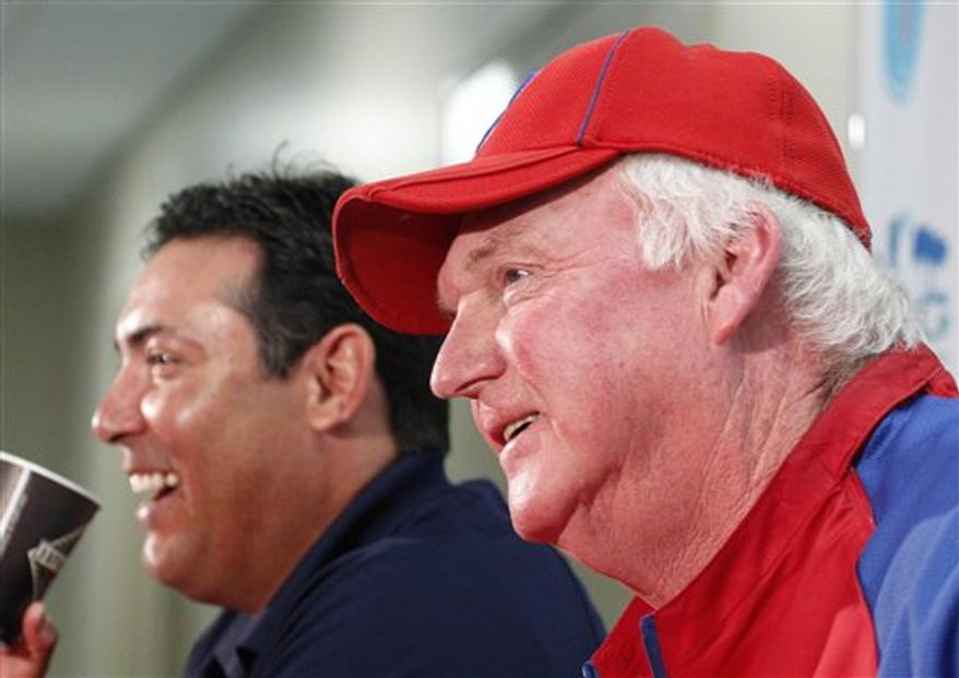 Philadelphia Phillies manager Charlie Manuel, right, talks with reporters after having a two-year contract extension announced by Phillies Senior Vice President and General Manager Ruben Amaro Jr., left, before a spring training baseball game against the New York Yankees in Clearwater, Fla., Thursday, March 10, 2011.  (AP Photo/Gene J. Puskar)