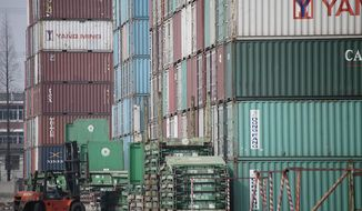 A forklift arranges shipping containers near a port in Shanghai on Wednesday, March 2, 2011. (AP Photo/Eugene Hoshiko)
