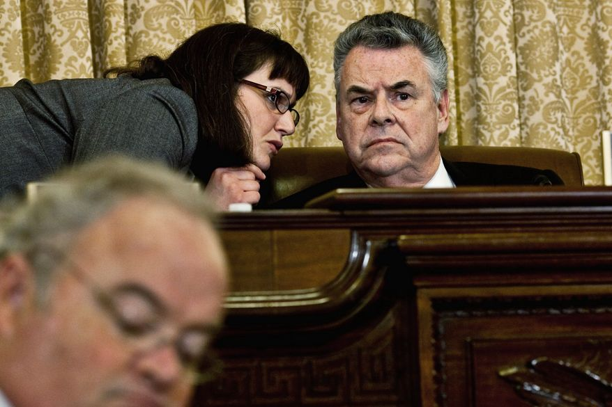 "Rep. Peter T. King, New York Republican and chairman of the House Homeland Security Committee, confers Thursday with an aide during a hearing, ""The Extent of Radicalization in the American Muslim Community and that Community's Response."" He said it was the first in a series of such hearings. (Drew Angerer/The Washington Times)"