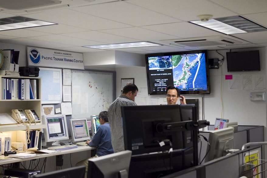 Workers are seen inside the Pacific Tsunami Warning Center, Thursday, March 10, 2011, in Honolulu. The Pacific Tsunami Warning Center in Hawaii has widened its tsunami warning to include Hawaii and the rest of the Pacific Ocean. The first waves were expected to arrive at 2:55 a.m. HST Friday. (AP Photo/ Marco Garcia)