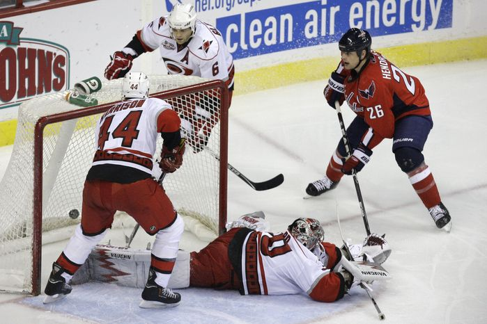 Carolina Hurricanes defenseman Jay Harrison (44), defenseman Tim Gleason (6), and goalie Cam Ward (30) react as Washington Capitals center Matt Hendricks (26) scores during the third period of an NHL hockey game at the Verizon Center in Washington on Friday, March 11, 2011. (AP Photo/Jacquelyn Martin)