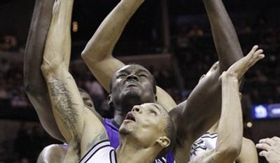 San Antonio Spurs' Tony Parker (9), of France, shoots over  Sacramento Kings' Eugene Jeter, right, during the second quarter of an NBA basketball game on Friday, March 11, 2011, in San Antonio. (AP Photo/Eric Gay)