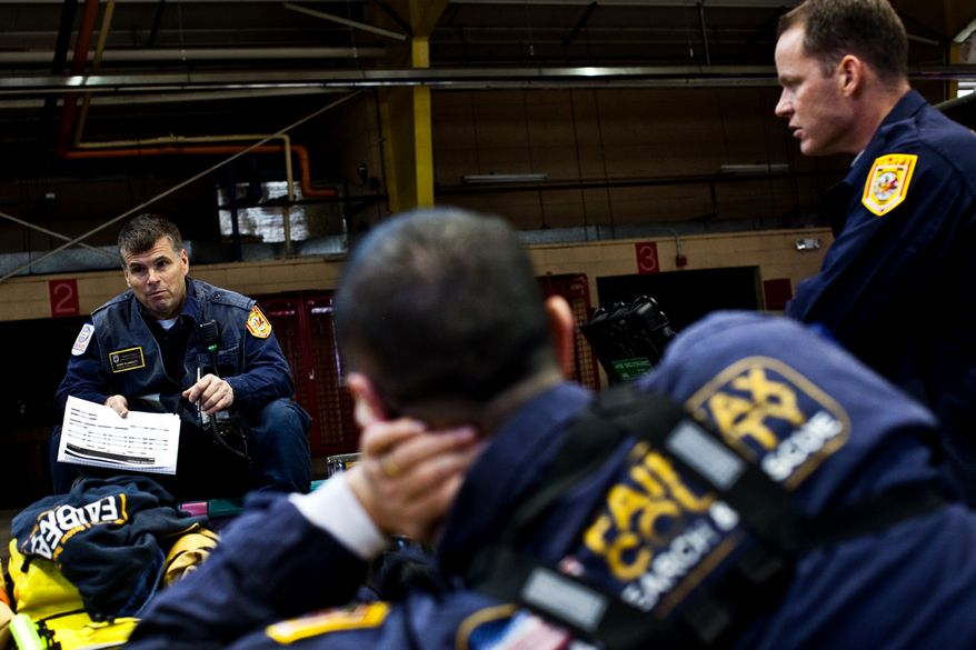 Rescue Squad officer Mark Plunkett, left, a Fairfax County fireman from Stafford, Virginia, briefs a unit on what to expect during their mission in Japan, at the Fairfax Fire and Rescue Training Facility, in Fairfax, Friday, March 11, 2011. (Drew Angerer/The Washington Times)