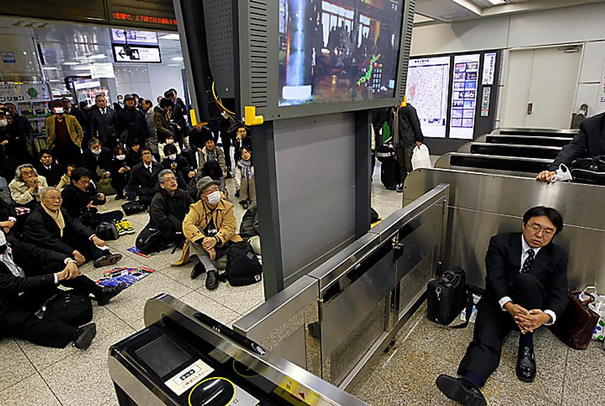 Stranded commuters watch a TV news on a powerful earthquake at Tokyo railway station as train services are suspended in Tokyo Friday, March 11, 2011. The largest earthquake in Japan's recorded history slammed the eastern coasts Friday. (AP Photo/Hiro Komae)