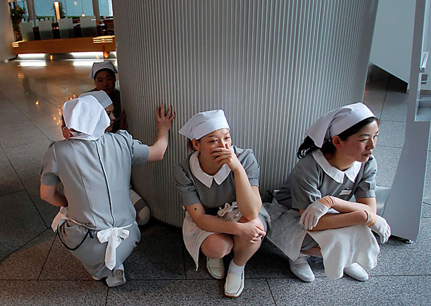 Hotel employees squat down in horror at the hotel's entrance in Tokyo after a strong earthquake hit Japan Friday, March 11, 2011. (AP Photo/Itsuo Inouye)