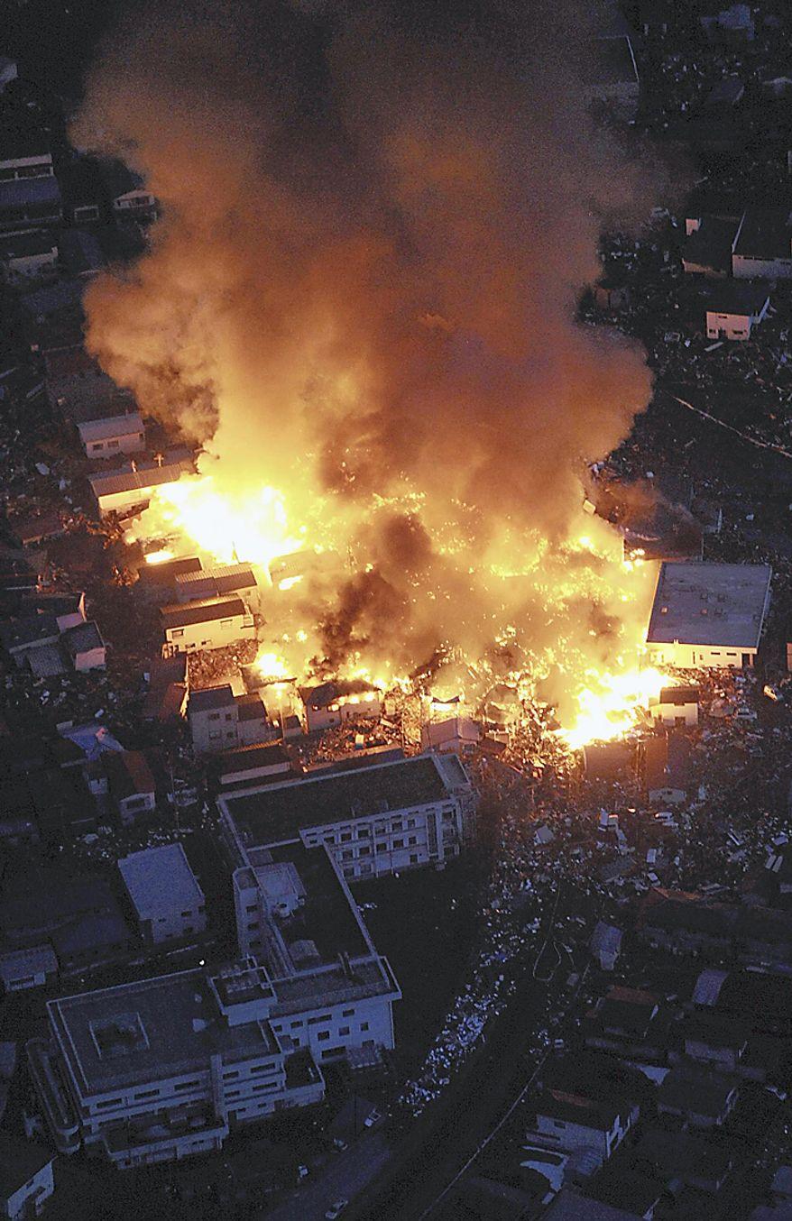 Flames rise from houses on fire after powerful earthquakes hit Yamada, Iwate Prefecture, northern Japan, Friday, March 11, 2011. (AP Photo/Osamu Kanazawa, The Yomiuri Shimbun)