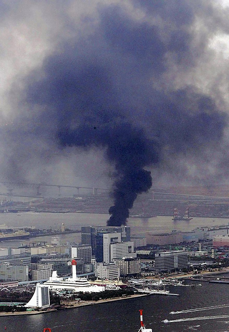 Black smoke rises from a building in Tokyo's Odaiba bay area after strong earthquakes hit Japan Friday, March 11, 2011. (AP Photo/Yasushi Kanno, The Yomiuri Shimbun)