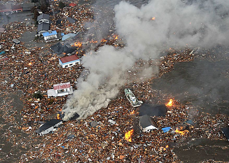 Flames rise from houses and debris half submerged in tsunami in Sendai, Miyagi Prefecture (state) after Japan was struck by a strong earthquake off its northeastern coast Friday, March 11, 2011. (AP Photo/Kyodo News)