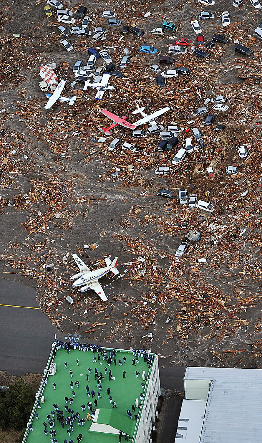 People seek refuge on the rooftop of a building as light planes and vehicles sit among the debris after they were swept by a tsunami that struck Sendai airport in northern Japan on March 11, 2011. A magnitude 8.9 earthquake slammed Japan's eastern coast Friday, unleashing a 13-foot (4-meter) tsunami that swept boats, cars, buildings and tons of debris miles inland. (Associated Press/Kyodo News)