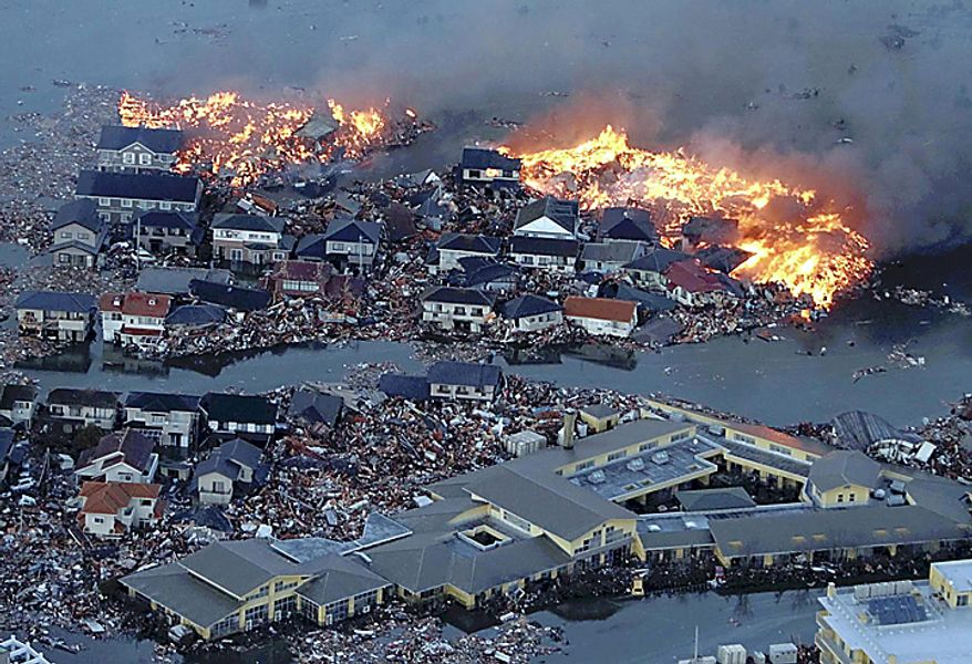 Houses are shown in flame while the Natori river floods over the surrounding area by tsunami tidal waves in Natori city, Miyagi Prefecture, northern Japan, March 11, 2011, after strong earthquakes hit the area. (AP Photo/Yasushi Kanno, The Yomiuri Shimbun)