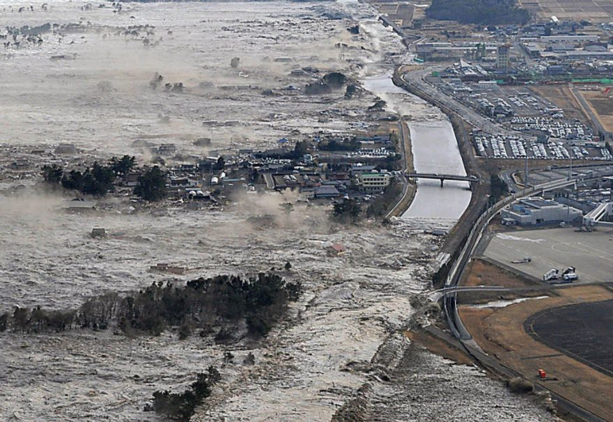 Earthquake-triggered tsunami waves sweep along Iwanuma in northern Japan on Friday March 11, 2022. The magnitude 8.9 earthquake slammed Japan's eastern coast Friday, unleashing a 13-foot (4-meter) tsunami that swept boats, cars, buildings and tons of debris miles inland. (AP Photo/Kyodo News)